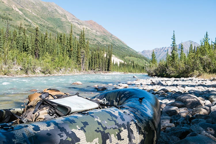 An inflatable camouflage-print raft sits on the rocky shores of a mountain river.