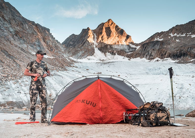 Matthew sets up his tent against the backdrop of a mountain glacier.
